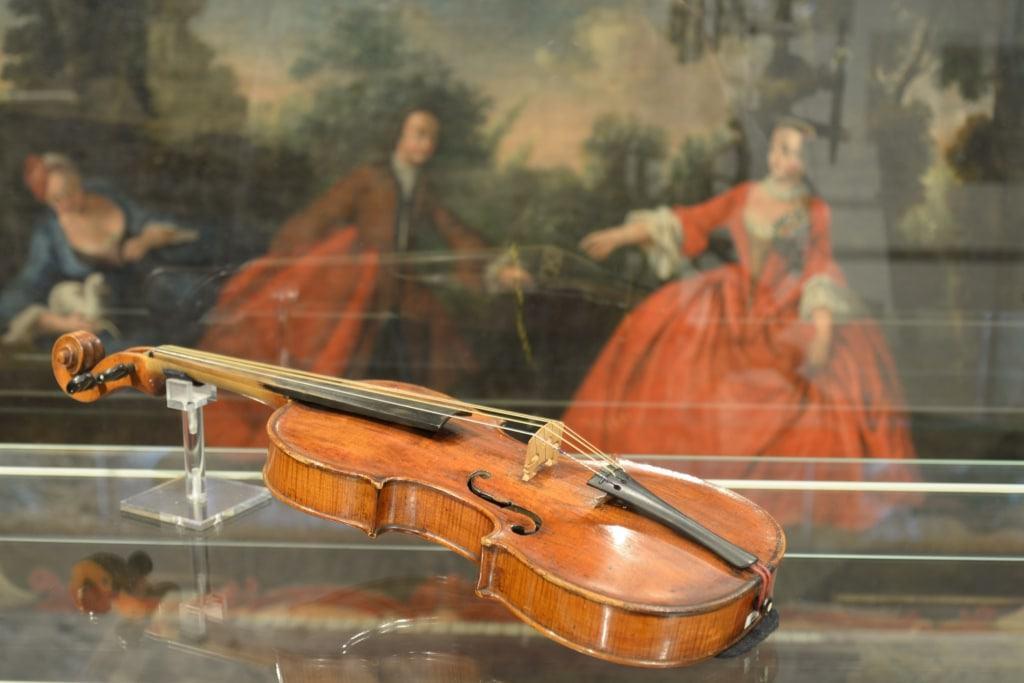 Im Vordergrund eine Geige als historisches Musikinstrument (um 1800), im Hintergrund eine Rokoko-Wandtapete aus einem Lüneburger Bürgerhaus – zwei Objekte aus der Zeit von Johann Abraham Peter Schulz (1747 - 1800) Foto: Museum Lüneburg