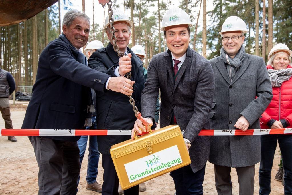 Norbert Tietz (von links), Landrat Rainer Rempe, Alexander Tietz und Hanstedts Samtgemeindebürgermeister Olaf Muus, lassen den Grundstein in die Erde ein. Foto: Adrian Fohl
