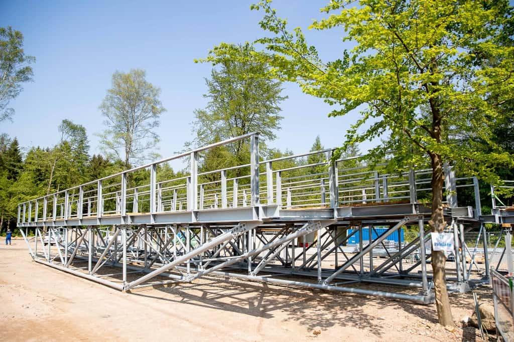 Im Anlieferungsbereich werden die einzelnen Brückenteile, Pfosten und Gehwegbeläge vormontiert, bevor sie per Kran auf die Fundamente gesetzt werden. Foto: Thomas Ix