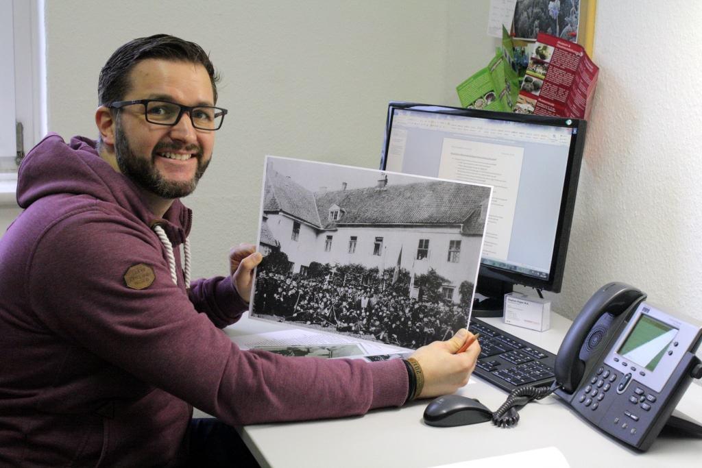 Volontär Stephan Pieper mit einem historischen Foto des Alten Kreishauses. Es zeigt eine Schützengesellschaft vor dem Kanzleiflügel des heutigen Museums. © Bachmann-Museum Bremervörde