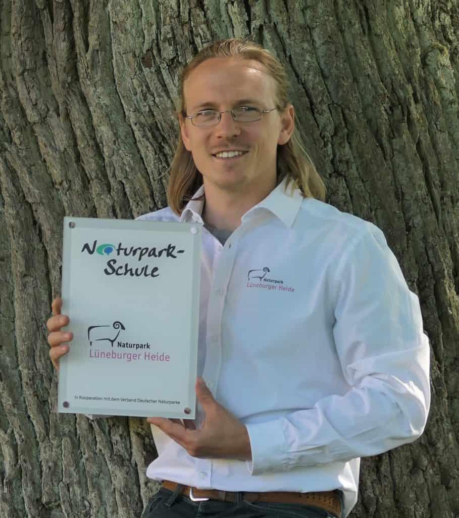 Robin Marwege, Projektleiter Bildung für nachhaltige Entwicklung beim Naturpark, mit der Auszeichnungsplakette für die Partner-Schulen. Foto © Naturpark Lüneburger Heide