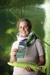 Claire Löchner mit ihrem Faltblatt zur Natur des Jahres vor dem Hechtbecken im Biosphaerium Elbtalaue, Foto Biosphaerium Elbtalaue