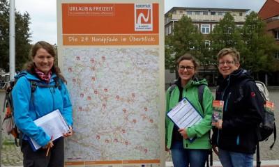 Liane Jordan und Tanja Brichacek vom Deutschen Wanderverband in Kassel  und Petra Welz von TourROW vor der Übersichtskarte der Nordpfade Copyright: TouROW