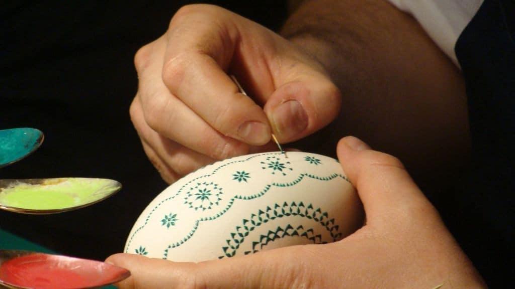 Männerhand malt ein kunstvolles Muster in grüner Farbe auf ein Osterei