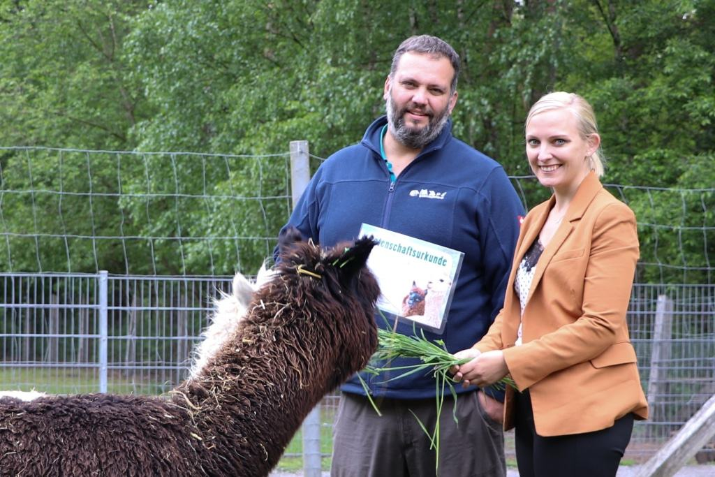 Die Sparkasse Celle hat die Patenschaft für die Alpakas übernommen. Thomas Wamser überreichte als Anerkennung die Patenschaftsurkunde an Marleen Tuttlies. Foto: Wildpark Müden