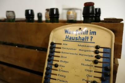 Emaillierte Einkaufsliste mit Schiebern aus der Sonderausstellung Einzelhandel im Museumsdorf Hösseringen